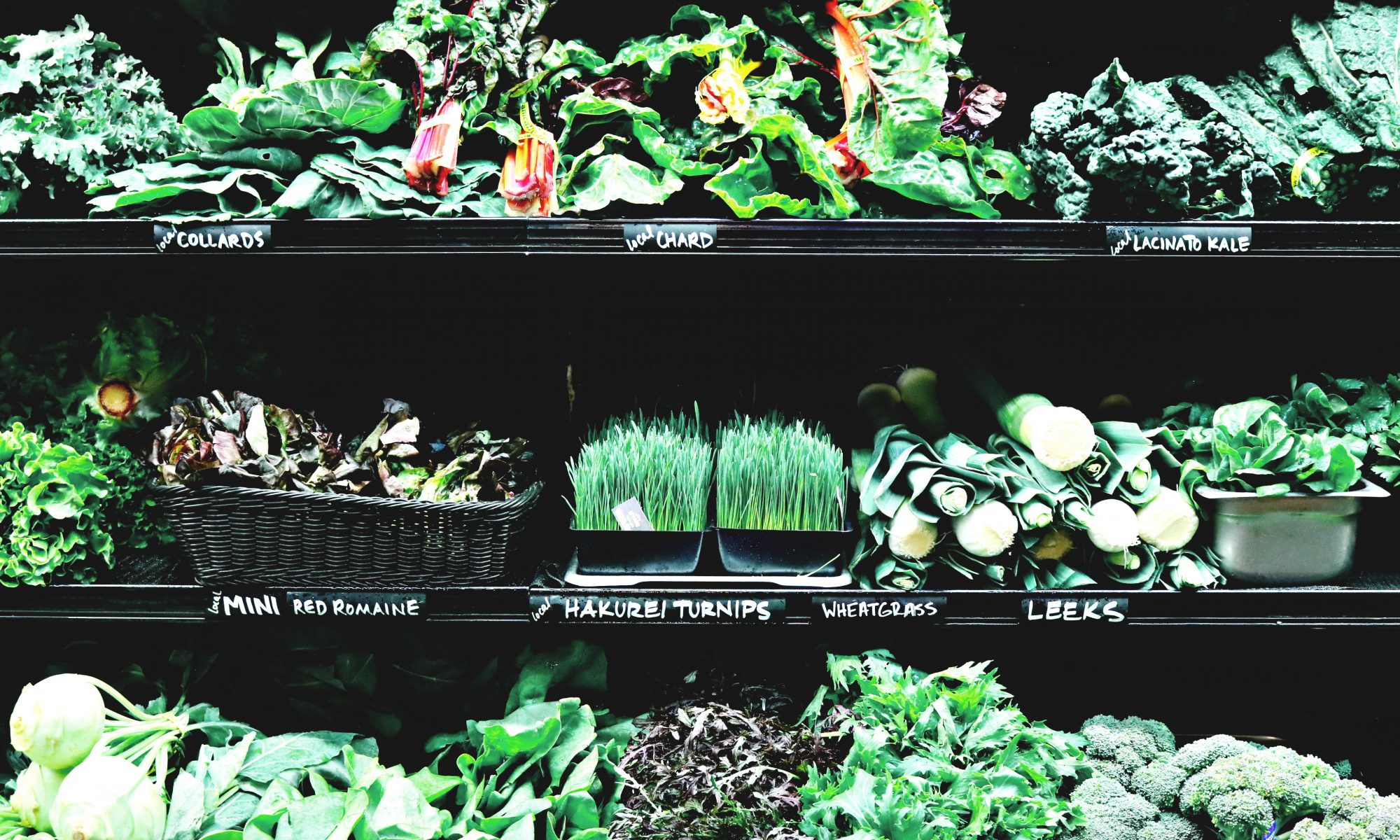 Image: On the background, various vegetables, collards, chard, lacinato kale, mini red romaine, hakurei turnips, wheatgrass, and leeks, on shelves.